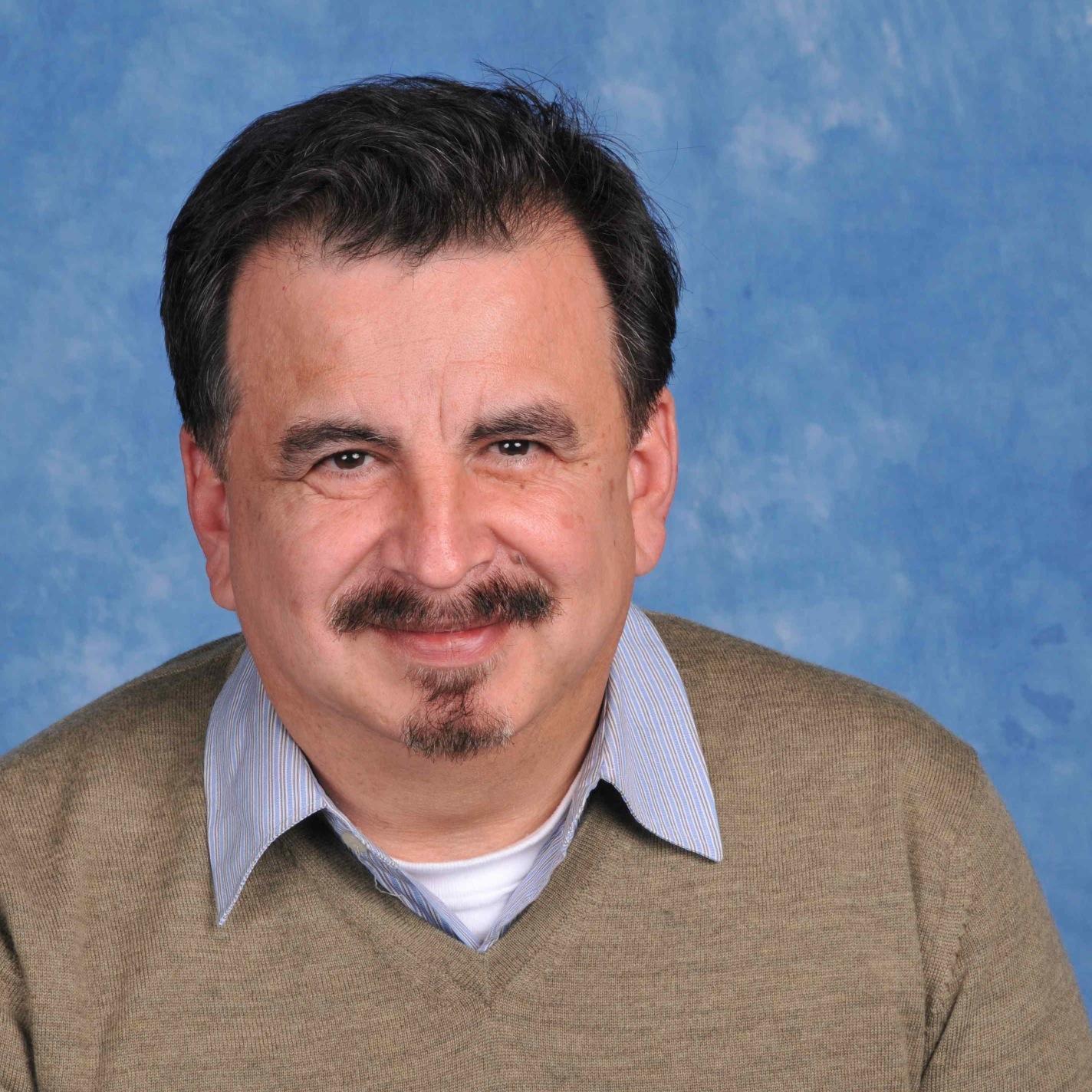 Photo of James Rojas; centered; mustache; goatee; beige sweater; light blue collared shirt.